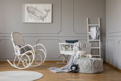 Grey whale on poster in stylish baby room interior with white wooden rocking chair and crib, copy space on empty wall