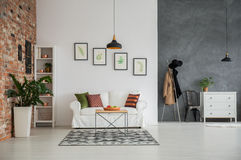 Grey and white loft interior. With couch, dresser and chair Royalty Free Stock Photo