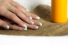 Grey with white nail asymmetry art manicure. Skin care of a beauty female hands with grey and white asymmetry nail art manicure  on a sackcloth and yellow candle Stock Photo