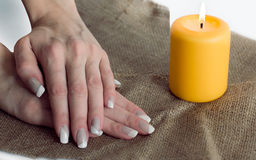 Grey with white nail asymmetry art manicure. Skin care of a beauty female hands with grey and white asymmetry nail art manicure  on a sackcloth and yellow candle Stock Photos