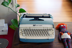 Grey and White Typewriter Near Blue and Orange Rugdoll during Daytime Stock Photo