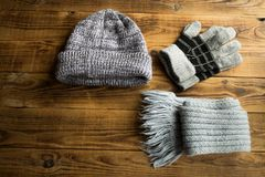 Grey winter hat gloves scarf on a wooden bacground. A grey winter hat gloves scarf on a wooden bacground Royalty Free Stock Photo