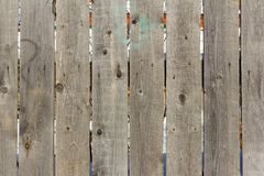 Grey wooden fence, old wooden fence made of old boards. Background, texture of old wooden planks, old rustic fence with slits between Royalty Free Stock Photos