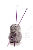 Grey wool and needles. Grey wool and purple needles  on white background Stock Photo