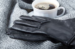 Grey wool scarf and gloves around the cup of coffee Stock Photos