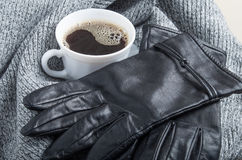 Grey wool scarf and leather gloves around the white cup of coffe Royalty Free Stock Image