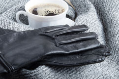 Grey wool scarf and leather gloves around the white cup of coffee. With blur and shallow depth of focus stock photos