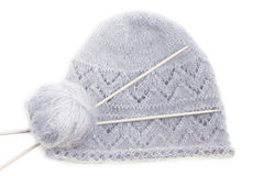 Grey woolen knitted cap with clew and needles Royalty Free Stock Images