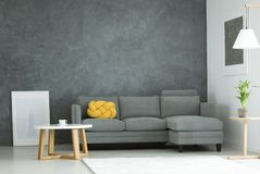 Grey and yellow living room. Yellow knot pillow on grey couch in cozy living room interior with poster and round wooden table Stock Image