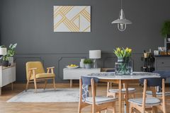 Grey and yellow open space. Chairs at wooden dining table with flowers in grey open space interior with yellow armchair Stock Images