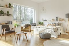 Grey and yellow open space. Grey and yellow wooden armchair in open space interior with bed and view on forest Royalty Free Stock Photos
