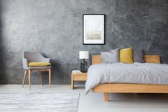 Grey and yellow room. With king-size bed, poster and lamp standing on bedside table Royalty Free Stock Photos