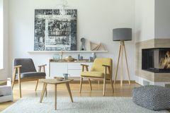 Grey and yellow living room. Grey and yellow wooden armchair in living room interior with patterned pouf near fireplace and lamp Royalty Free Stock Image