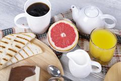 Greyfrut and toast for breakfast. Breakfast with coffee and orange juice, grapefruit, toast and chocolate spread Stock Images