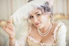 Greyhead woman in white dress with pale skin on rococo background. A vampire woman with a beautiful hairdo with a feather and pen stock photos