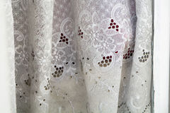 Greyish curtain with hole embroidery in an old window, background Stock Images