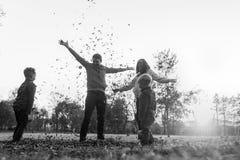 Greyscale изображение молодой семьи играя с листьями осени стоит стоковые фото
