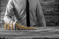 Greyscale beeld die van zakenman dalende domino's tegenhouden Stock Fotografie