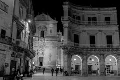 Greyscale Horizontal View of a Street Illuminated By Artificial. Light at Night and The Church Dome on Background. Martina Franca, South of Italy Stock Photo
