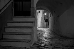 Greyscale Horizontal View of a Street Illuminated By Artificial. Light at Night With Stone Stairs and an Arch. Martina Franca, South of Italy Royalty Free Stock Image