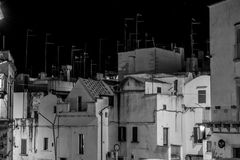 Greyscale Horizontal View of White Houses with a lot of Televisi. On Analogic Antennas Illuminated By Artificial Light at Night. Martina Franca, South of Italy Stock Images