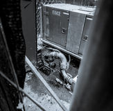 Greyscale image of junkyard, water flowing from industrial pipe Royalty Free Stock Image