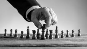 Greyscale image of a male hand reaching dark queen chess piece Stock Image