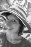 Greyscale image of a smiling woman in an elegant straw sunhat. Under the shade of a tree in summer Stock Images