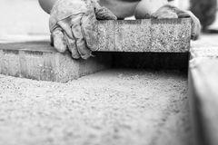 Greyscale image of workman laying a paving brick Royalty Free Stock Image