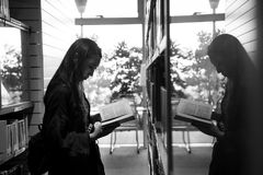 Greyscale Photo of Girl Reading a Book Reflecting on a Glass royalty free stock image
