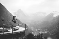 Greyscale Photo of Man Jumping Near Metal Rail and Mountain at Daytime Stock Image