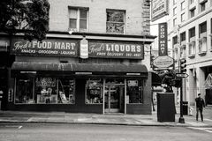 Greyscale Photo of Man Standing on Road Near Fred's Liqours Building royalty free stock image