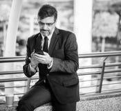 Greyscale Photo Of Man Wearing Suit Jacket And Eyeglasses Holding Smartphone Royalty Free Stock Photography