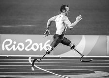 Greyscale Photography of Man With Artificial Legs Running on Concrete Pavement Stock Photo
