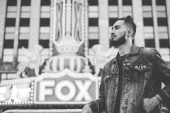Greyscale Photography of a Man in Denim Jacket Standing in Front of Fox Building Royalty Free Stock Image