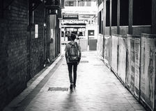Greyscale Photography of a Man Walking Down an Alley Royalty Free Stock Image