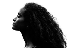 Greyscale portrait of a gorgeous proud young woman. Greyscale head shot portrait in profile of a beautiful proud young woman with gorgeous curly black hair royalty free stock image