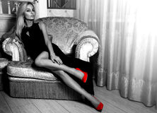 Greystyle picture of Adorable hot blonde woman in long black dre Stock Images