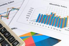 Gráficos y cartas del informe de ventas mensual con la calculadora Imagen de archivo libre de regalías