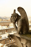 Notre Dame,Paris. Grgoyle on Notre Dame Cathedral in Paris with Montmartre in the background Royalty Free Stock Photography