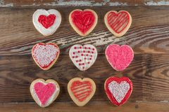 Grid of Decorated Heart Cookies. Over wooden table top stock images