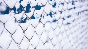 Grid fence in the snow. a lot of snow on the iron fence stock photo