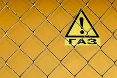 Grid fence with a warning sign - `Gas` in Russian. stock photos