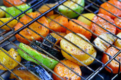 On the grid grill are fried vegetables. Potatoes, tomatoes, peppers, eggplants, cucumbers, zucchini, carrots and seasonings with o Royalty Free Stock Photography