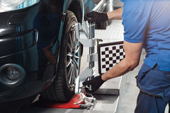 Grid sensor sets mechanic on auto. Car stand with sensors wheels for alignment camber check in workshop of Service. Grid sensor sets mechanic on auto. Car on stock photography