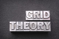 Grid theory bm. Grid theory phrase made from metallic letterpress blocks on black perforated surface Stock Photo