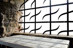 Grid in the window of the castle. Lattice in the window of a medieval castle over a rough wooden table isolated on a white background royalty free stock images