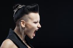 Grida arrabbiati della giovane donna isolati su fondo nero Fotografia Stock