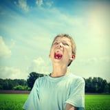Grida felici del bambino all'aperto Immagini Stock