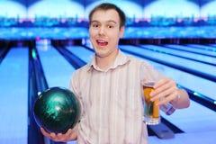 Grida felici dell'uomo, sfera delle strette e vetro di birra Immagine Stock